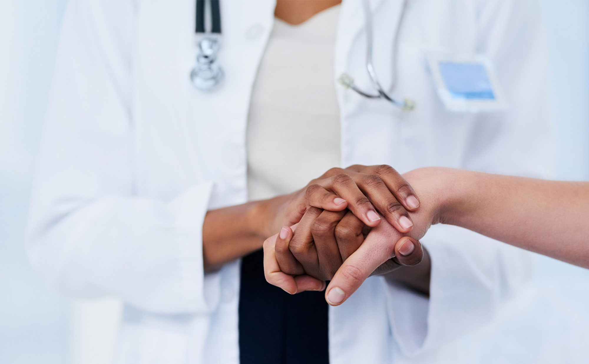 A medical professional holding onto a patient's hand.